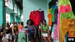 Archivo 2013. Dos comerciantes esperan la llegada de clientes en un negocio privado de venta de ropa importada, antes de que prohibieran la venta de estas. .