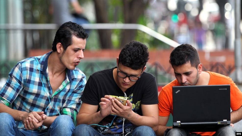 Jóenes se conectan a Internet en zona Wi Fi