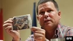 Omar Rodríguez, uno de los periodistas cubanos que han sido excarcelados y expatriados a España por el Gobierno de la isla, muestra un recorte de una revista durante una rueda de prensa en Madrid.