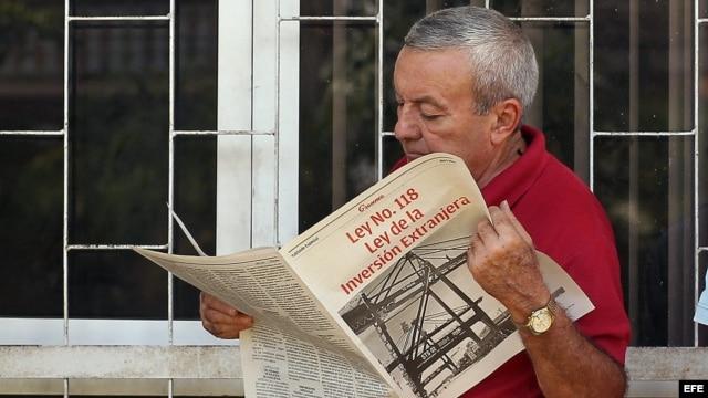 """Un hombre lee la edición especial del """"Granma"""", donde se divulga la Ley de Inversión Extranjera (abril, 2014)."""