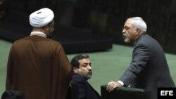 El ministro iraní de Asuntos Exteriores, Javad Zarif (dcha), conversa con un diputado mientras participa en la sesión parlamentaria convocada para hablar del acuerdo nuclear en Teherán, Irán