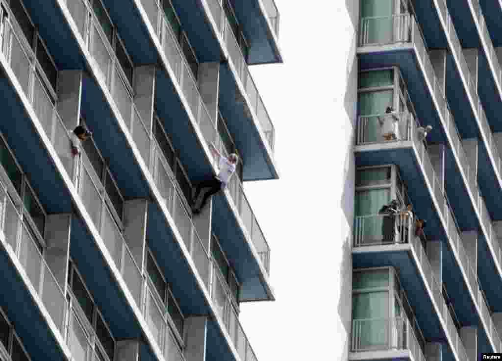 Cuando llegó al piso 15, se apartó un poco de la columna por la que estaba subiendo para saludar a unos trabajadores que se encontraban en un balcón.