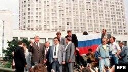 Foto de archivo, tomada el 19 de agosto de 1991, que muestra al presidente ruso, Boris Yeltsin (i), sobre un tanque aparcado frente a un edificio de la Federación Rusa, mientras sus seguidores sostienen una bandera de la Federación Rusa.