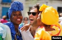 Modelos vestidas al estilo colonial besan a un turista en La Habana.
