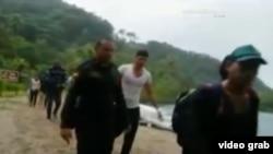 Policías colombianos conducen a un grupo de 16 cubanos que trataban de cruzar a pie la frontera con Panamá.