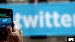 Un transeúnte toma fotografías al logo de la red social Twitter.