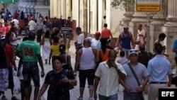 Varias personas caminan por una céntrica calle, junto a una Casa de Cambio, en La Habana (Cuba).