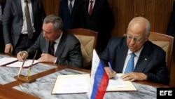 El vicepresidente cubano Ricardo Cabrisas Ruiz (d) y el vicepresidente de Rusia, Dmitry O. Rogozyn(i), firman los acuerdos.