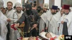 CRISIS EN SLAVIANSKUn guerrillero armado prorruso echa flores sobre los cuerpos de tres hombres durante el funeral celebrado en una iglesia ortodoxa de Slaviansk, Ucrania, el 22 de abril del 2014.
