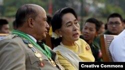 Aung San Suu Kyi (d) conversa con el general Zaw Win (i), viceministro de Asuntos Fronterizos, durante el desfile por el Día de las Fuerzas Armadas en Birmania.