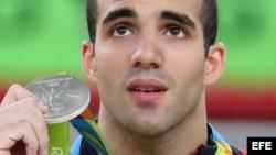 Danell Leyva muestra la medalla de plata que ganó hoy en el evento de barras paralelas en Río 2016