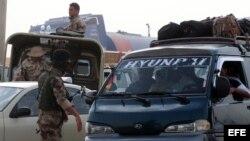 Hombres armados vigilan y controlan a iraquíes que dejan el area de violencia en Mosul en un reten en Erbil en la región del Kurdistan (Irak).