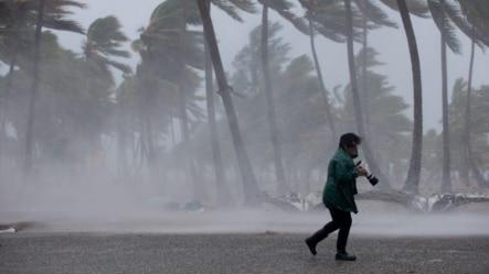 Una mujer camina bajo la lluvia a la llegada de la tormenta tropical Erika a República Dominicana el viernes.