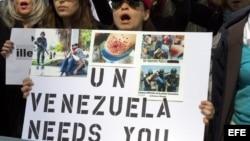 Decenas venezolanos protestan con pancartas y fotografías de personas agredidas por la Policía venezolana frente a la sede de la ONU en New York.