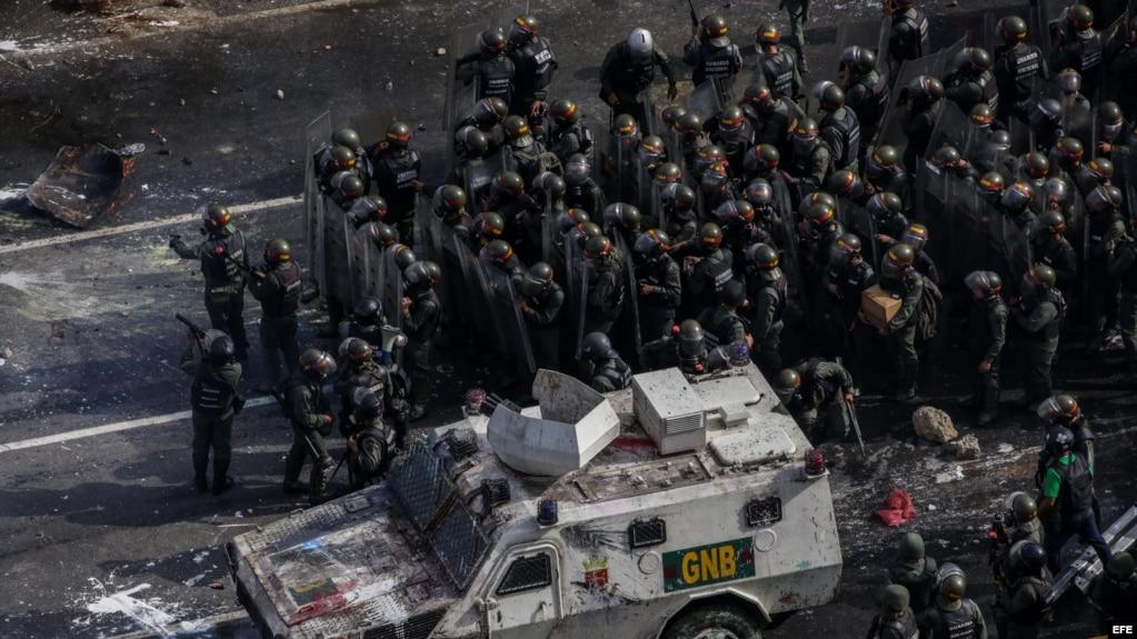 Miembros de la Guardia Nacional Bolivariana (GNB) se enfrentan a manifestantes opositores el sábado, 27 de mayo de 2017, en Caracas.