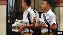 Dos estudiantes caminan con sus libros.