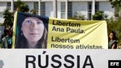 Simpatizantes del grupo ecologista Greenpeace sostienen pancarta con una imagen de la activista brasileña Ana Paula durante una protesta frente a la embajada de Rusia en Brasilia (Brasil).