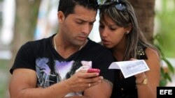 Dos jóvenes usan un teléfono móvil en La Habana. (Archivo)