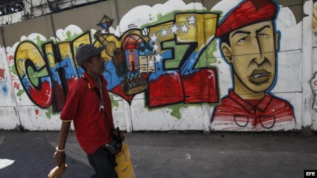 Transeúntes caminan frente a pintadas de apoyo al presidente Hugo Chávez, en el centro de Caracas, Venezuela
