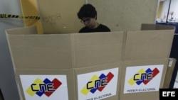 Miembros de mesa y testigos electorales trabajan durante los preparativos de un centro electoral en Caracas, de cara a las elecciones presidenciales de mañana domingo 14 de abril en Venezuela