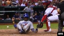 El jardinero derecho de los Dodgers de Los Ángeles Yasiel Puig anota una carrera ante el receptor Tony Cruz (d)