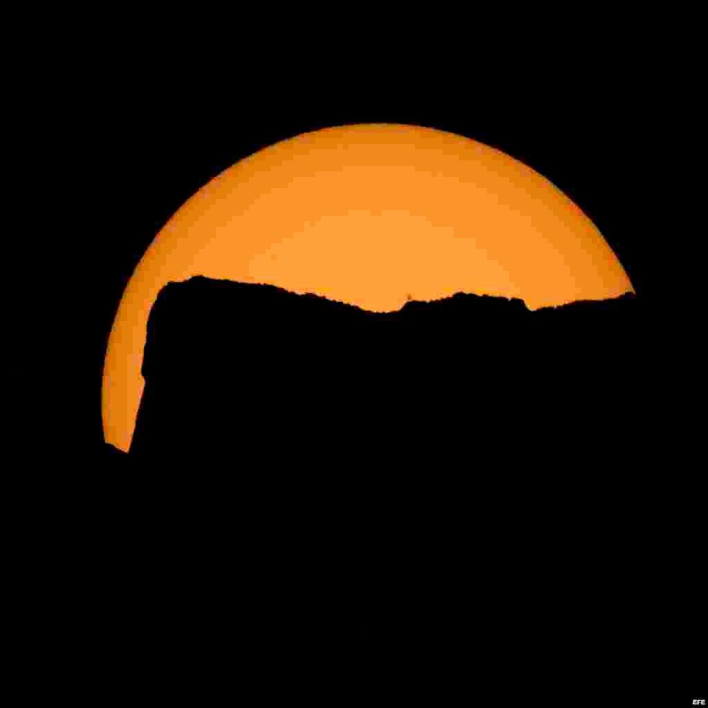 Fotografía cedida por la NASA que muestra una puesta de sol antes del eclipse total en el parque nacional Northern Cascades en Washington.