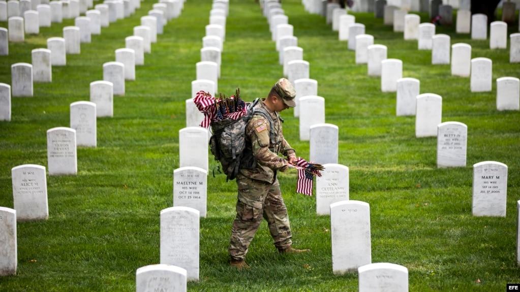 Soldados depositan banderas americanas en cada lápida durante una ceremonia por el Día de los caídos, en el Cementerio Nacional de Arlington, en Virginia.