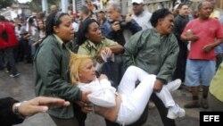 Fotografía de archivo de una integrante de las Damas de Blanco cuando era trasladada a la fuerza a un autobús de la policía.EFE/Rolando Pujol