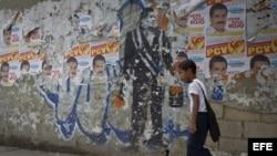 Un niño camina junto a un grafitti en tributo al fallecido presidente venezolano Hugo Chávez en una calle de Caracas (Venezuela).