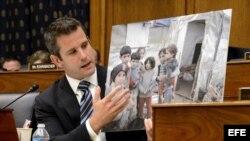 El congresista Republicano por Illinois, Adam Kinzinger, sostiene una fotografía de niños sirios que describe afectados por el gas sarín.