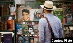 Un turista revisa viejos libros revolucionarios ofrecidos por un cuentapropista.