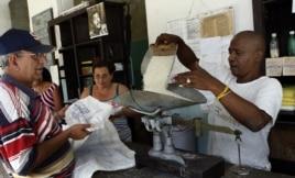 Un bodeguero despacha a un anciano los productos que se distribuyen mediante la libreta de racionamiento en Cuba.