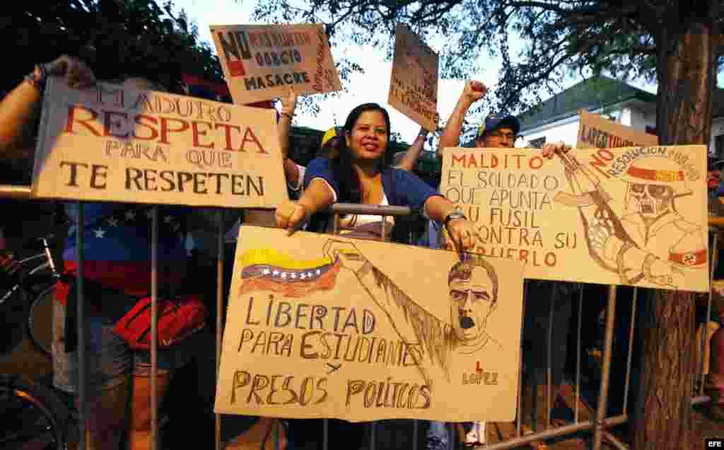 Manifestantes sostienen pancartas hoy, jueves 12 de febrero de 2015, durante una movilización en contra del Gobierno de Nicolás Maduro frente a la Embajada de Venezuela, en Santiago (Chile). En el aniversario de las primeras manifestaciones estudiantiles