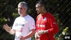 El jugador de la selección nacional de Chile Arturo Vidal (d) habla con el fisioterapeuta Jose Amador (i) durante el entrenamiento.