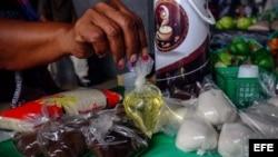 Una vendedora informal sostiene una bolsa de aceite vegetal, que ofrece a la venta junto a azúcar y café en un puesto en una calle de Caracas.