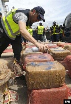 Un agente de la Agencia Tributaria marca los fardos con los 2.400 kilos de cocaína incautados.
