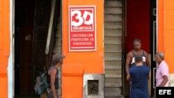 Varios hombres conversan en la puerta de un cine 3D de propiedad privada en La Habana (Cuba).