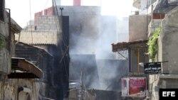 Una humareda sale de un edificio dañado en el barrio de Midan, en Damasco, Siria, el día 20 de julio de 2012.