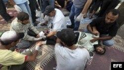 Un miembro herido de los Hermanos Musulmanes recibe tratamiento médico tras los enfrentamientos con las fuerzas de seguridad, en El Cairo, Egipto, hoy, lunes 8 de julio de 2013. Al menos 51 personas murieron y otras 435 resultaron heridas en los choques,