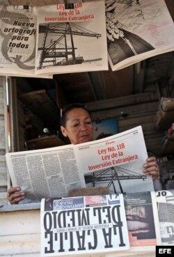 Una vendedora de periódicos lee un tabloide especial confeccionado por el diario Granma donde se divulga la nueva Ley de Inversión Extranjera.