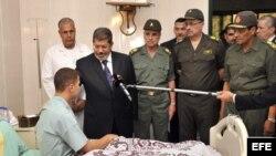 El presidente Mohamed Morsi (2-i) visita a una soldado egipcio que fue herido en un ataque en la región fronteriza de Rafah, en un hospital de El Cairo, Egipto hot, martes 7 de agosto de 2012.