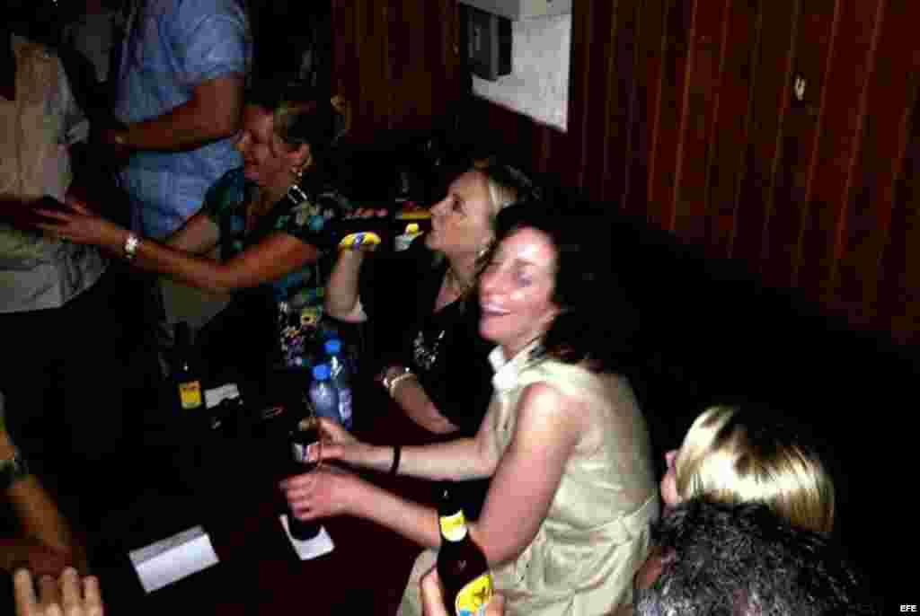 La secretaria de Estado de Estados Unidos, Hillary Clinton (c), tomando cerveza, durante una fiesta en Cartagena (Colombia).