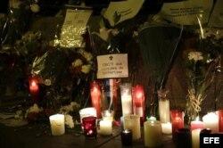Flores, velas y mensajes depositados ante la puerta de la Embajada de Francia en España, en el centro de Madrid.