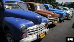 Detalle de varios viejos autos de fabricación estadounidense convertidos en taxi particular.