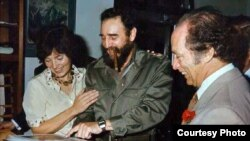 Fidel Castro y Pierre y Margaret Trudeau miran un album fotográfico durante la visita oficial a Cuba de los Trudeau en enero de 1976.