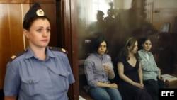 """Las tres integrantes del grupo de punk """"Pussy Riot"""" Nadezhda Tolokonnikova (2ª izq), Yekaterina Samutsevich (der) y Maria Aliokhina (2ªder) en el banquillo de los acusados en una zona acristalada, a la espera de que comience la sesión de juicio en el juzg"""