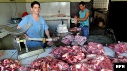 Archivo - Dos hombres venden carne en La Habana (Cuba).