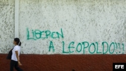 Un hombre camina junto a un muro donde aparece un grafiti pidiendo la liberación del dirigente político venezolano opositor Leopoldo López hoy, jueves 5 de junio del 2014, en el municipio de Chacao, en Caracas.