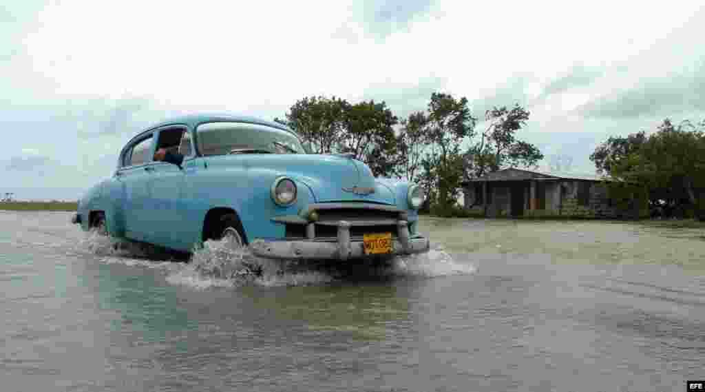 Un auto pasa sobre las aguas desboradas del rio La Rosita, Matanzas (Cuba).