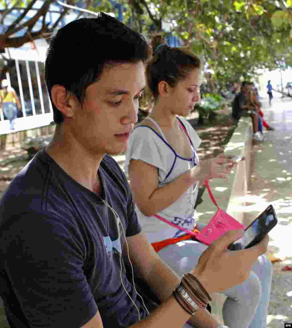 Dos jóvenes navegan por internet desde un dispositivo móvil hoy, viernes 3 de julio del 2015, en una de las zonas habilitadas con Wi-Fi en La Habana.